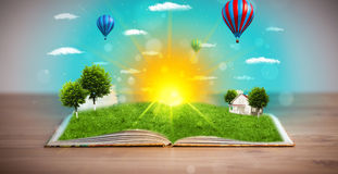 Open book with green nature world coming out of its pages Stock Image