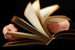 Open book in hands. Looking thruogh book with motion blur on black background Royalty Free Stock Image