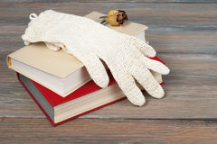Open book, hardback books on wooden table, rose and white gloves knitted crochet Back to school. Copy space for text. Royalty Free Stock Images