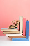 Open book, hardback colorful books on wooden table, red, pink background. Back to school. Copy space for text. Education. Open book, hardback colorful books on stock photography
