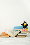 Open book, hardback colorful books on wooden table. Toy crow. Back to school. Copy space for text. Education business. Concept royalty free stock photo