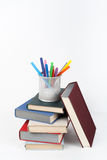 Open book, hardback colorful books on wooden table, white background. Back to school. Pens, pencils, cup. Copy space for Royalty Free Stock Images