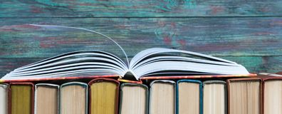Open book hardback on Stack books. On wooden background. Back to school with copy space stock image