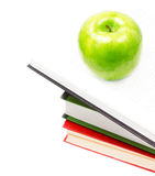 Open Book heap and green apple on top over white background. Con Royalty Free Stock Images