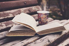 Open book and hot drink on wooden bench in autumn park Royalty Free Stock Photo