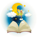 An open book with an image of a fairy and a sleeping moon Stock Photography