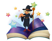 An open book with an image of a scary witch holding a cane Royalty Free Stock Photography