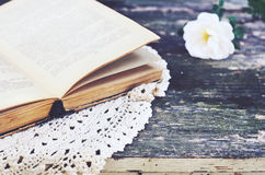 Open book on lace doily on rusted garden table Royalty Free Stock Image