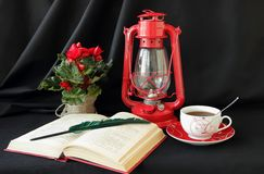 Open book, lamp and a cup of tea Royalty Free Stock Photos