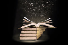 Open book with letters falling into the pages. An open book with letters falling into the pages Stock Images