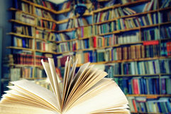 Open book in a library. Selective focus