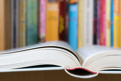 Open book with a library in background. An open book in foreground with a blurred colorful library in background Stock Image