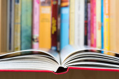 Open book with a library in background. An open book in foreground with a blurred colorful library in background Stock Photography