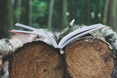 An open book lies on felled trees save trees - read ebooks conce Royalty Free Stock Photo