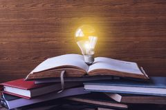 Open book with light bulb and hardback books on wood wall background. stock photos