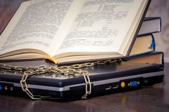 An open book is lying on a laptop that is linked by a chain. Books instead of computers. Love to read_. An open book is lying on a laptop that is linked by a royalty free stock photo