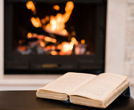 Open book lying near the fireplace Royalty Free Stock Photography