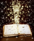 Open book with magic light and magic letters. And drawings Stock Photos
