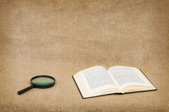 Open book and magnifier on canvas Stock Photography