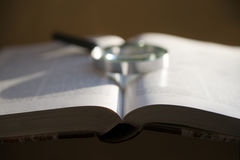 Open book with magnifying glass Royalty Free Stock Image