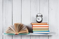 Open book, multi-coloured books and alarm clock. Stock Photos