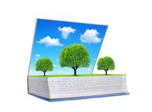 Open book of nature with trees on meadow and blue sky isolated on white background. stock photo