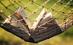 Open book nobody in a hammock. Various objects of the summer season in the best of this wonderful period Royalty Free Stock Photo