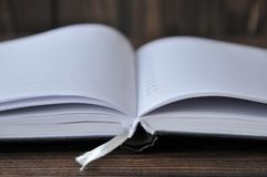 Open book or notebook lies on a wooden table royalty free stock photo