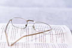 Open book with old glasses Stock Images
