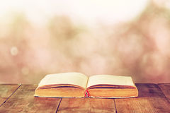Open book over wooden rustic table in front of blurred bokeh lights Stock Photo
