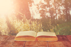 Open book over wooden rustic table in front of wild landscape and sunset light burst Royalty Free Stock Photo