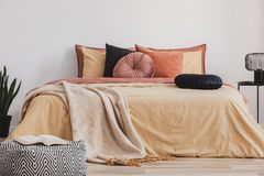 Open book on patterned pouf in colorful bedroom interior stock photo