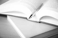 Open book with pen black and white color tone style. Open book with pen on wood background black and white color tone style Royalty Free Stock Photos
