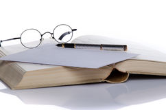 Open book with a pen and glasses. On white Royalty Free Stock Photo