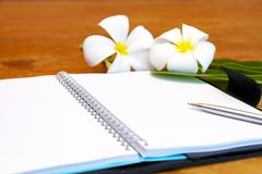 Open book,pen and Plumeria. In pot on wooden desk.Taking notes is a memorandum.Many important lessons learned from the recording stock photos