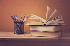 Open book and pencils on wooden deck table Stock Image