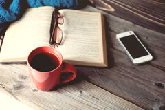 Open book with phone, glasses and coffee or tea top view on table Stock Image