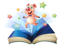 An open book with a pig jumping happily Royalty Free Stock Image