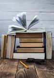 Open book on a pile of books with glasses and pencil royalty free stock photos