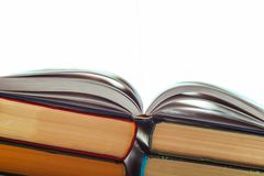 An open book on a pile of other books. Concept for education. Pure white light coming out of an open book royalty free stock images