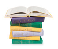 Open book on a pile of vintage books in multicolored covers Stock Photo