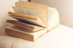 Open book on a pillow in bed. homeliness. old book. seamless texture of book pages. Vintage old books Stock Photo