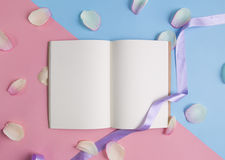 Open book with pink petals on pastel background. Stock Photography