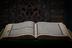Open book of Quran - Koran with mosque in background Stock Photos