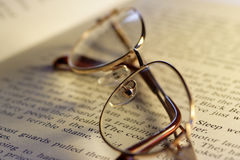 Open book and reading glasses Stock Image