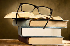 Open book with reading glasses Stock Image
