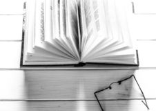 Open book ready to read lies on a white wood table next to the old round glasses royalty free stock photo