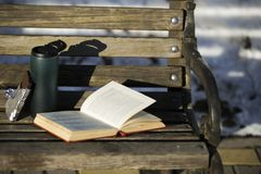 An open book in a red cover, a glass cup with a lid with coffee stock image