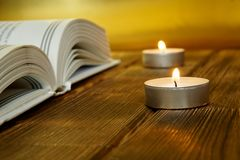 An open book about religion and faith lies on wooden planks on a golden background. Nearby are lit candles. Close-up stock photography