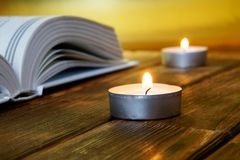 An open book of religious content lies on wooden boards against a golden background. Nearby are lit candles royalty free stock photos